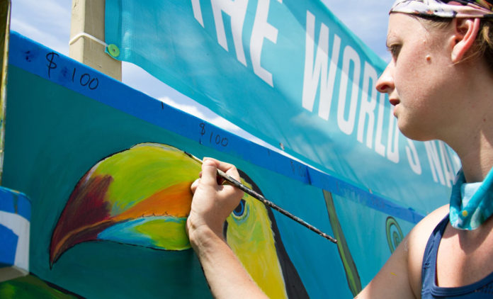 An artist paints the Forecastle Foundation mural during the Forecastle Festival.